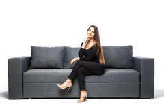 Woman sitting with hands on chin on sofa on white background royalty free stock photos