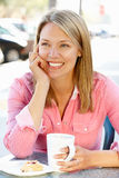 Woman sitting having coffee at cafe Stock Images