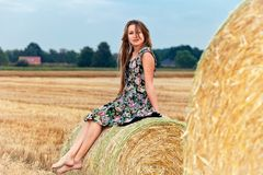 Woman  sitting on hay bale Stock Photography