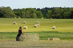 Woman Sitting on Hay Bale. Woman sitting on a hay bale after harvest Stock Image