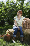Woman Sitting On Hay Bales Near Orchard Stock Images