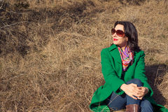 Woman sitting on the hay in a green coat Royalty Free Stock Photography