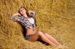 Woman sitting on haystack Stock Images