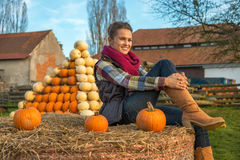 Woman sitting on haystack with pumpkin in front of Stock Image