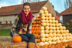 Woman sitting on haystack with pumpkin in front of Royalty Free Stock Photo