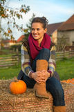 Woman sitting on haystack with pumpkin Stock Photo