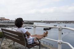 Woman sitting on her back with her legs up on a bench in a cudillero fishing port stock photos