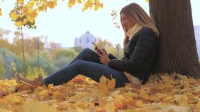 Woman Sitting With Her Back To The Tree In Yellow Fall Leaves, Uses Smartphone. Joyful young brunette woman sitting with her back to the tree on the yellow stock video footage