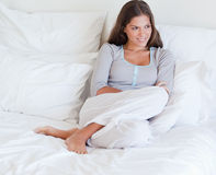 Woman sitting on her bed Stock Photography