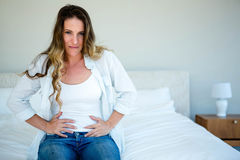 Woman sitting on her bed gripping her  stomach Stock Photo