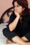 Woman sitting in her bed with a sad expression Royalty Free Stock Photography