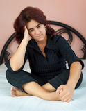 Woman sitting on her bed with a sad expression Stock Photography
