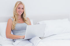 Woman sitting on her bed while using her laptop Royalty Free Stock Photography