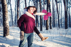 Woman is sitting on her boyfriend`s back. In winter forest Stock Photo
