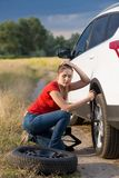 Young woman sitting at her car with flat tire trying to unscrew wheel nuts. Woman sitting at her car with flat tire trying to unscrew wheel nuts Royalty Free Stock Image
