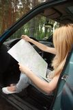 Woman sitting by her car and looking at map Stock Image