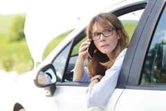 Woman sitting in her car on the road. Portrait of middle aged woman sitting in her broken down car and using mobile phone while waiting for help Royalty Free Stock Images