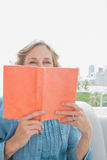 Woman sitting on her couch covering face with orange book Royalty Free Stock Images