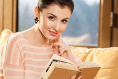 Woman sitting on her couch at home and reading a book Stock Photo