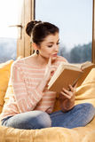 Woman sitting on her couch at home and reading a book Royalty Free Stock Image