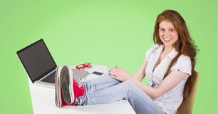 Woman sitting on her desk against green background Royalty Free Stock Photography