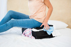 Woman sitting on her overfull suitcase. At home Royalty Free Stock Images