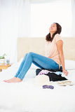 Woman sitting on her overfull suitcase. At home Stock Images