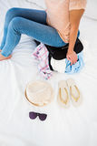 Woman sitting on her overfull suitcase. At home Royalty Free Stock Photo
