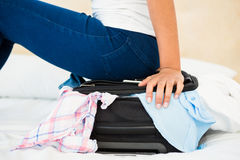 Woman sitting on her overfull suitcase. At home Stock Photo