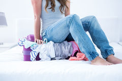 Woman sitting on her suitcase Stock Photography