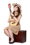Woman sitting on her suitcase while playing guitar Royalty Free Stock Image