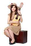 Woman sitting on her suitcase while playing guitar Royalty Free Stock Photos