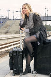 Woman sitting on her suitcase at train station Stock Photography