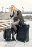 Woman sitting on her suitcase at train station Stock Photo