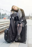 Woman sitting on her suitcase at train station Royalty Free Stock Photos