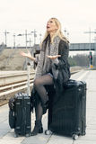 Woman sitting on her suitcase at train station looking upset Stock Images