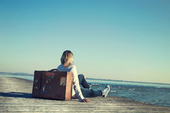 Woman sitting on her suitcase waiting for the sunset in a specta Stock Photo