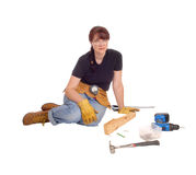 Woman sitting with her tools. A middle age woman sitting on the floor and working with some tools Royalty Free Stock Image