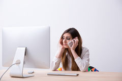 Woman sitting at her workplace with smartphone Stock Image