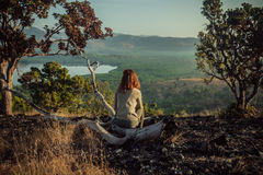 Woman sitting on a hill at sunrise Royalty Free Stock Image