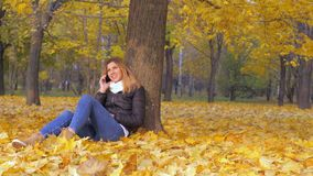 Woman Sitting With His Back To Tree In Yellow Autumn Leaves, Talking Smartphone. Lovely young brunette woman sitting with her back to the tree on the yellow stock footage