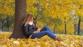 Woman Sitting With His Back To The Tree In Yellow Autumn Leaves, Uses Smartphone. Pretty young brunette woman sitting with her back to the tree on the yellow stock video