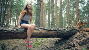 Woman sitting with his dangling legs. Young girl with a backpack in the summer in the woods. Woman sitting with his dangling legs on the tree felled. Slow motion stock video footage