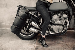 Woman sitting on his motorcycle. Motorcycle near the garage. Leather bag and jeans. Motorcycle black. The woman`s legs Stock Photos