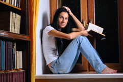 Woman is sitting and holding a book Royalty Free Stock Photo