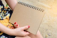 Woman holding a book. Woman sitting and holding a book Royalty Free Stock Photos