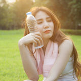 Woman Sitting and holding a bottle of water. Royalty Free Stock Photos