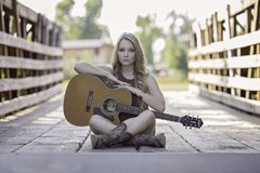 Woman Sitting While Holding Classical Guitar during Daytime Stock Image