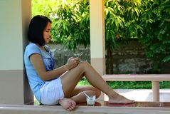 A woman sitting and holding mobile in the morning of holiday w royalty free stock photo