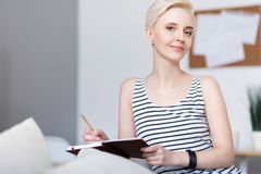 Woman sitting and holding notebook Stock Images